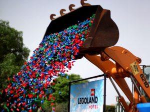 Een bulldozer dropt duizenden bouwsteentjes voor het Legoland-hotel