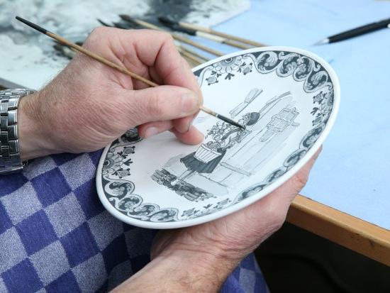 Een schilder van Royal Delft aan het werk met een Efteling-bordje